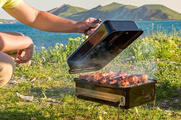 Cozinhando na churrasqueira. ao ar livre. perto da praia do mar e das montanhas