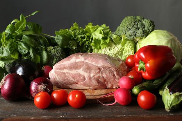 Cozinhando na cozinha variedade de vegetais e carne crua em uma placa