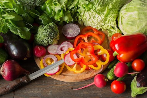 Cozinhando na cozinha. variedade de vegetais e pimentões picados e cebolas vermelhas em uma placa