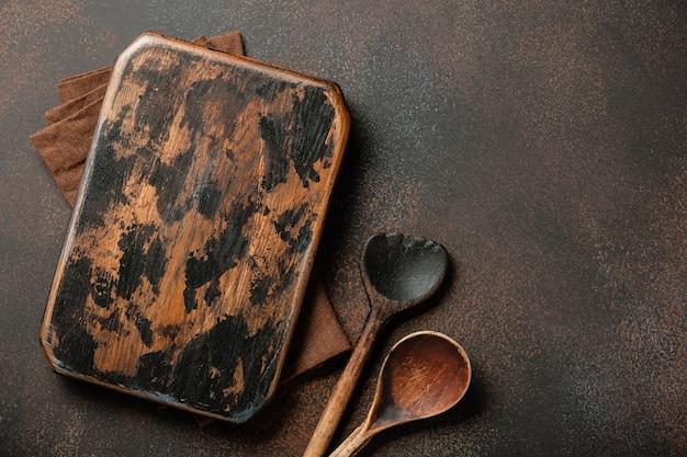 Cozinhando o fundo com uma tábua de corte vintage e colheres de madeira