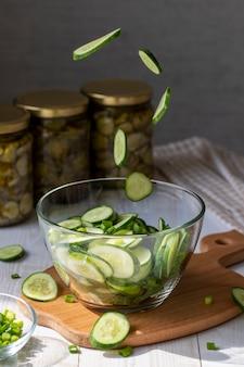Cozinhando salada com pepinos frescos voando fatias de pepino em um prato de vidro para salada