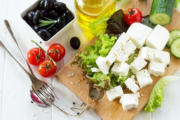 Cozinhando salada qreek com legumes frescos, queijo feta e azeitonas pretas em uma mesa de madeira branca