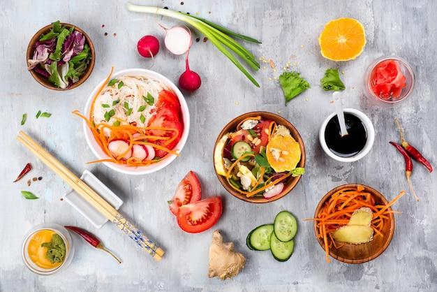 Cozinhando saladas vegetais sortidos e prato asiático no fundo de pedra,
