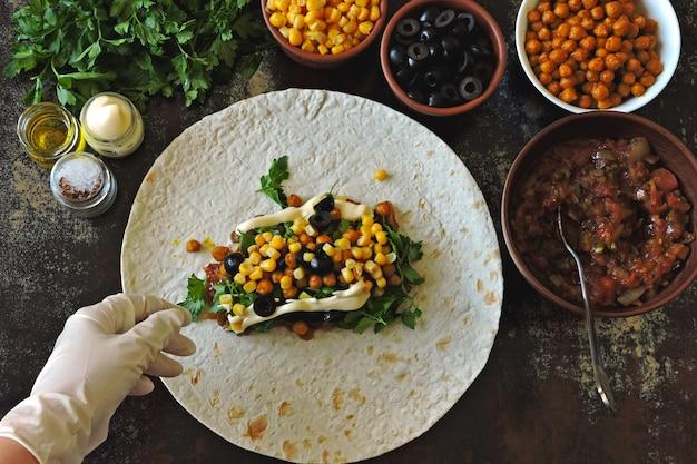 Cozinhando shawarma vegano. as mãos em luvas culinárias impõem um recheio no pão pita para fazer shawarma. cozinha do oriente médio.