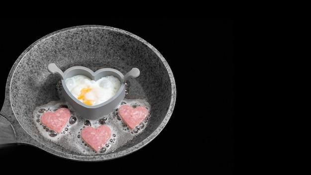 Cozinhando um delicioso café da manhã com ovos mexidos e salsichas em forma de coração em uma frigideira cinza