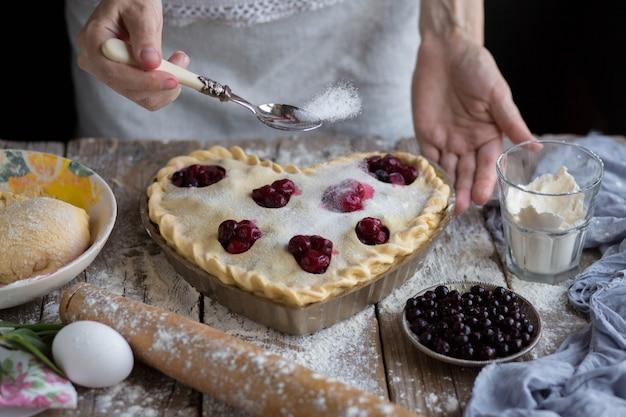 Cozinhando uma torta. torta fechada. o processo de fazer uma torta. cozimento em casa. mamãe assa. polvilha açúcar sobre o bolo. dispersão de açúcar. polvilhe o bolo com açúcar