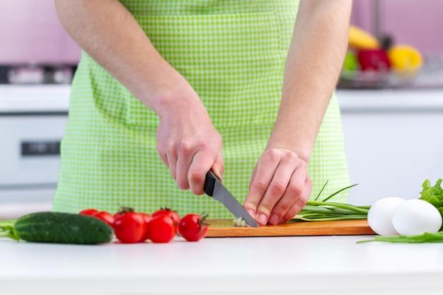 Cozinhar a pessoa no avental picar produtos amigáveis do eco para salada de legumes frescos saudáveis na cozinha em casa.