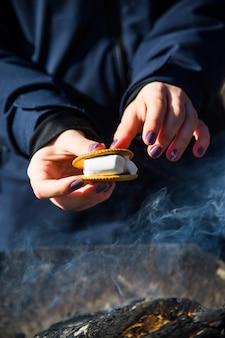 Cozinhar a sobremesa com marshmallows pelo fogo em um piquenique na natureza