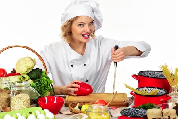 Cozinhar alimentos saudáveis. cozinheira feminina preparando comida deliciosa na cozinha. mulher com uniforme de chef.