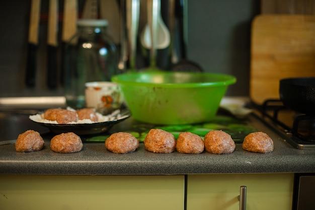 Cozinhar almôndegas, mentiras picadas prontas assando na mesa da cozinha