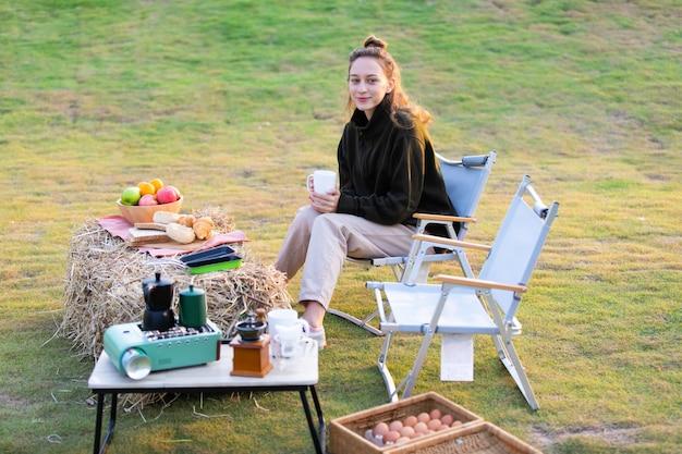 Cozinhar ao ar livre em acampamento. jovem casal caucasiano cozinhando e tomando café pela manhã