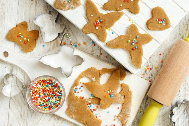 Cozinhar biscoitos com cortadores de biscoitos em uma mesa branca