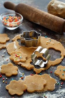 Cozinhar biscoitos com cortadores de biscoitos em uma mesa escura