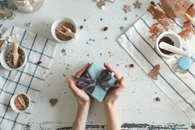 Cozinhar biscoitos de gengibre na véspera de natal em casa cozinha com um presente