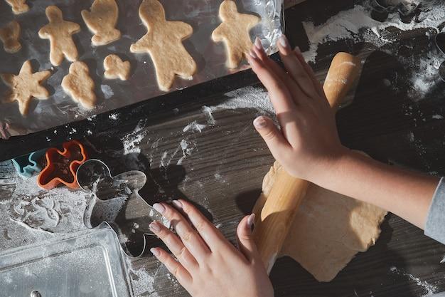 Cozinhar biscoitos de natal na mesa de madeira marrom escura. família fazendo homem-biscoito, cortando biscoitos de massa de pão de gengibre, vista de cima.