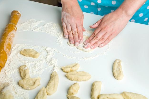 Cozinhar bolinhos de massa com purê de batatas na cozinha de casa.