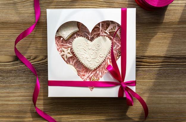 Cozinhar bolo maravilhosamente embrulhado com um grande laço. pão de ló decorado com flores frescas e biscoitos