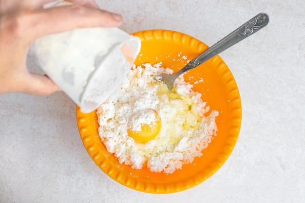 Cozinhar bolos de queijo, despeje farinha em um copo amarelo com queijo cottage fresco e um ovo