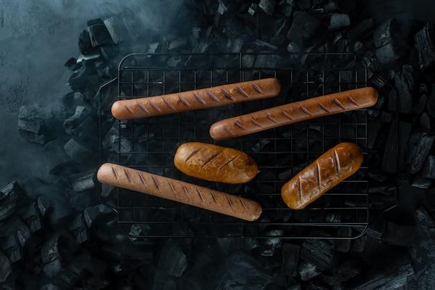 Cozinhar cachorros-quentes, salsichas na grelha, um fundo de fumaça e carvão