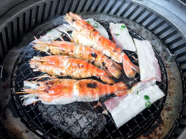 Cozinhar camarões grelhados com grelhador a carvão de forno por grelhados em grelha de aço. abaixo está o carvão que está muito quente.