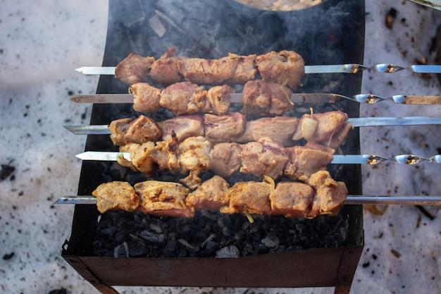 Cozinhar carne no fogo. shish kebab na grelha. a grelha é acesa no exterior no inverno. espetinhos fritos na grelha