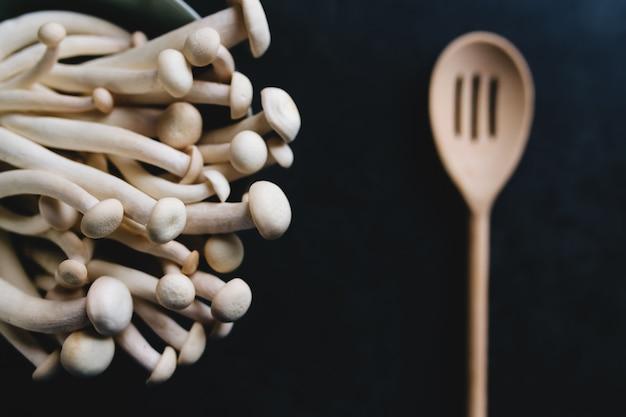 Cozinhar cogumelos brancos e colher de pau