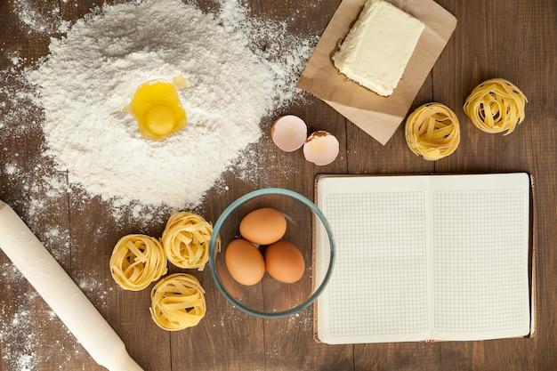 Cozinhar comida saborosa e escrever a receita em nota clara e aberta. com ingredientes como manteiga, ovos, farinha, macarrão.