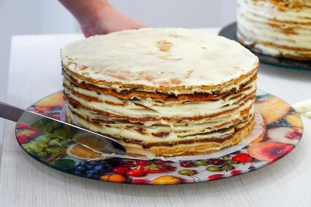 Cozinhar e nivelar bolos de aniversário festivos multicamadas. scones são manchados com chantilly. cook - confeiteiro.