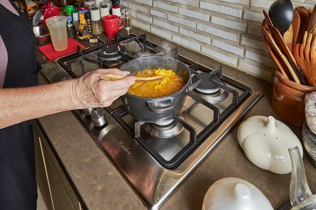 Cozinhar em casa na cozinha segundo receita da internet. mulher está mexendo o risoto em uma frigideira. receita passo a passo.