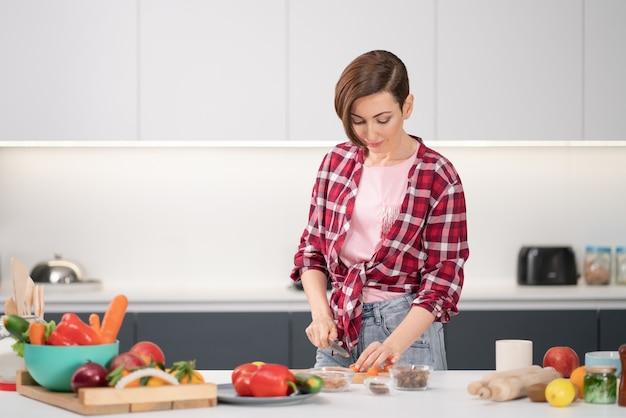 Cozinhar em casa para uma família amorosa. bela jovem cortando ingredientes na mesa cozinhando um almoço