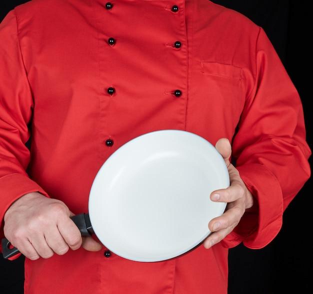 Cozinhar, em, vermelho uniforme, segurando, um, vazio, redondo, branca, frigideira
