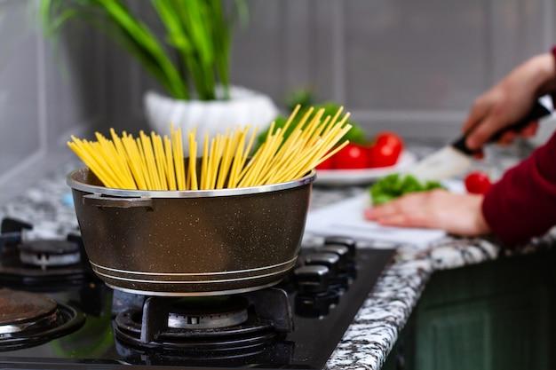 Cozinhar espaguete em uma panela em uma cozinha em casa