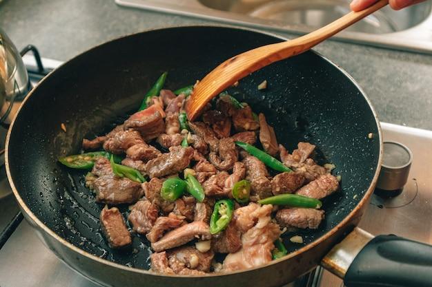 Cozinhar frite a carne com pimenta verde na panela de teflon.