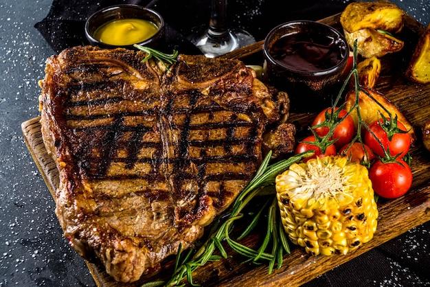 Cozinhar fundo de carne. carne fresca grelhada em fundo de mesa cinza escuro. vista do topo. copie o espaço