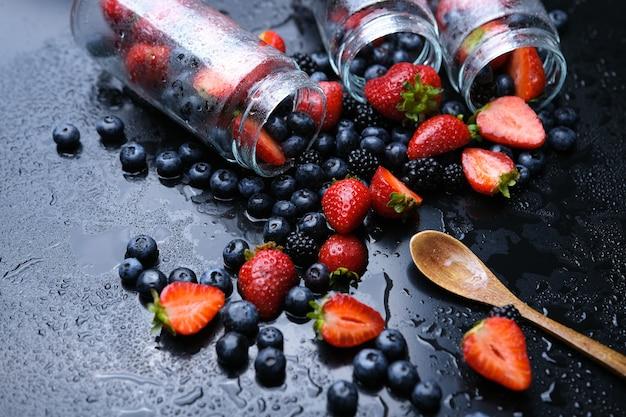 Cozinhar geléia de framboesa e mirtilo. cozinhando em uma jarra de vidro. rotação em um fundo preto.