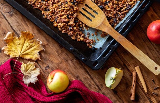 Cozinhar granola com maçã e especiarias em uma mesa de madeira