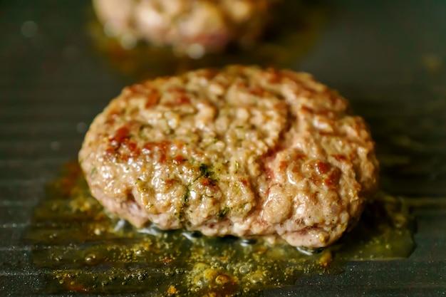 Cozinhar hambúrgueres de carne com especiarias na grelha em casa. feche acima, foco seletivo