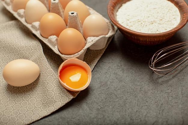 Cozinhar ingredientes de cozinha, farinha, ovos e têxteis de cozinha em fundo cinza de pedra. vista superior, copie o espaço.