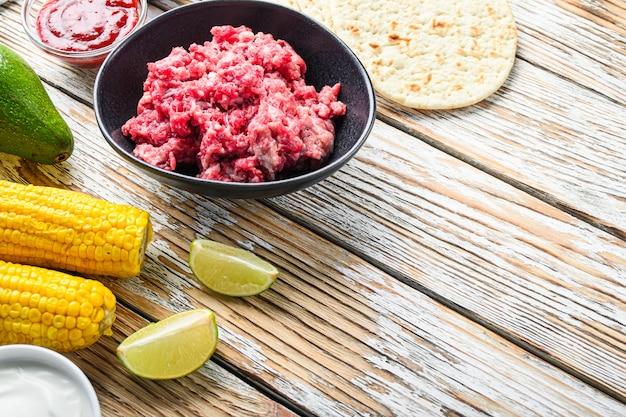 Cozinhar ingredientes mexicanos do taco com carne orgânica picada na tigela preta, milho, calsa sobre a mesa de madeira texturizada branca, vista lateral com espaço para texto.