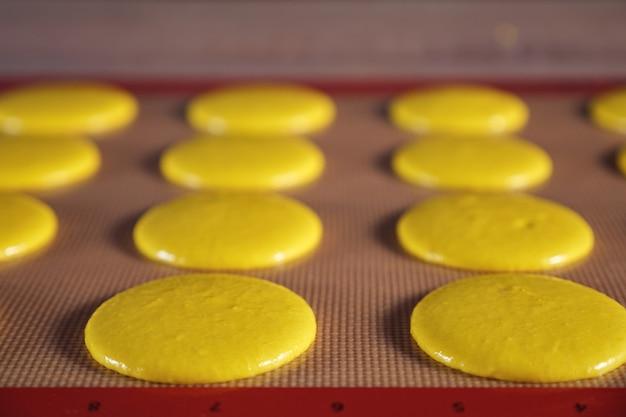 Cozinhar macaroons na esteira de silicone de estêncil em cima da mesa, close-up. foco seletivo