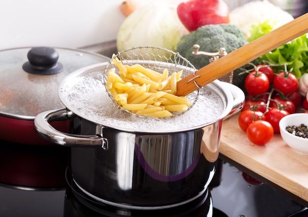 Cozinhar macarrão em uma panela com água fervente em um fogão na cozinha