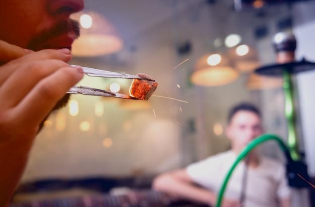 Cozinhar narguilé no bar. jovem com cachimbo de água no restaurante, bar de cachimbo de água, café de fumar.