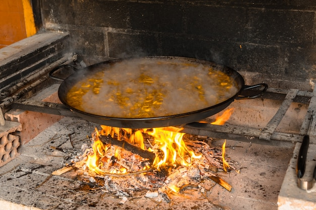Cozinhar o arroz da paella valenciana com brasas e legumes