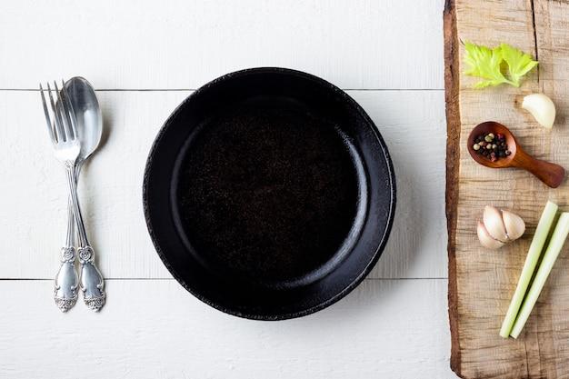 Cozinhar o conceito de plano de fundo. placa de ferro fundido preto rústico vazio, especiarias e talheres sobre fundo de madeira.