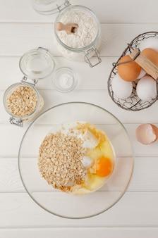 Cozinhar panquecas de aveia com bananas. ovos, leitelho, açúcar, baunilha, farinha de aveia em uma tigela sobre um fundo branco de madeira. receita passo a passo.