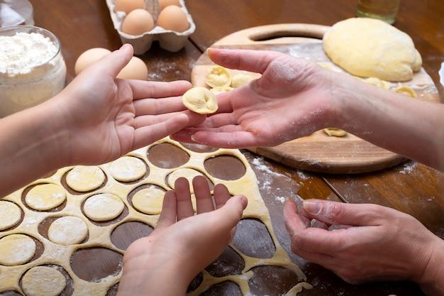 Cozinhar ravioli de massa e carne com toda a família. mãos de mulheres e crianças. bolinhos caseiros.