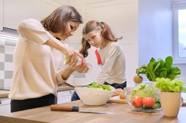 Cozinhar refeição saudável em casa pela família, salga de mulher e salada de pimenta