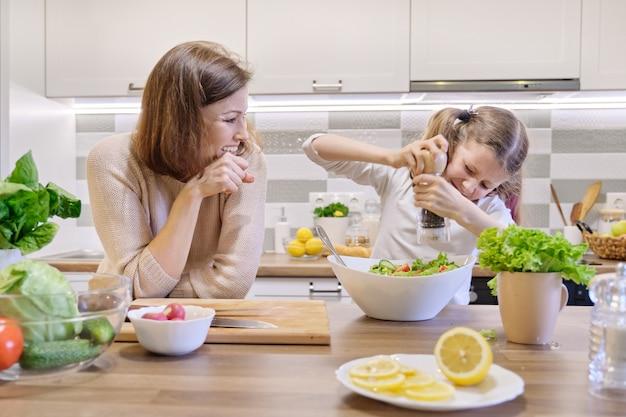 Cozinhar refeição saudável em casa por família. menina sais salada recém cozida, mãe olha para cima e se alegra