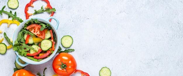 Cozinhar salada de legumes, legumes em uma tigela azul sobre uma superfície de concreto