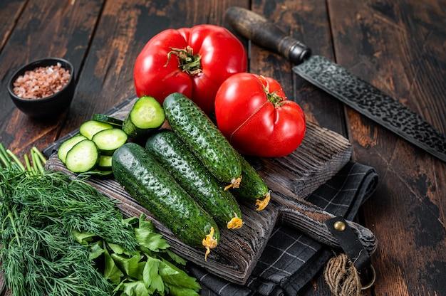 Cozinhar salada de legumes verdes com tomate, pepino, salsa, ervas. fundo de madeira escuro. vista do topo.